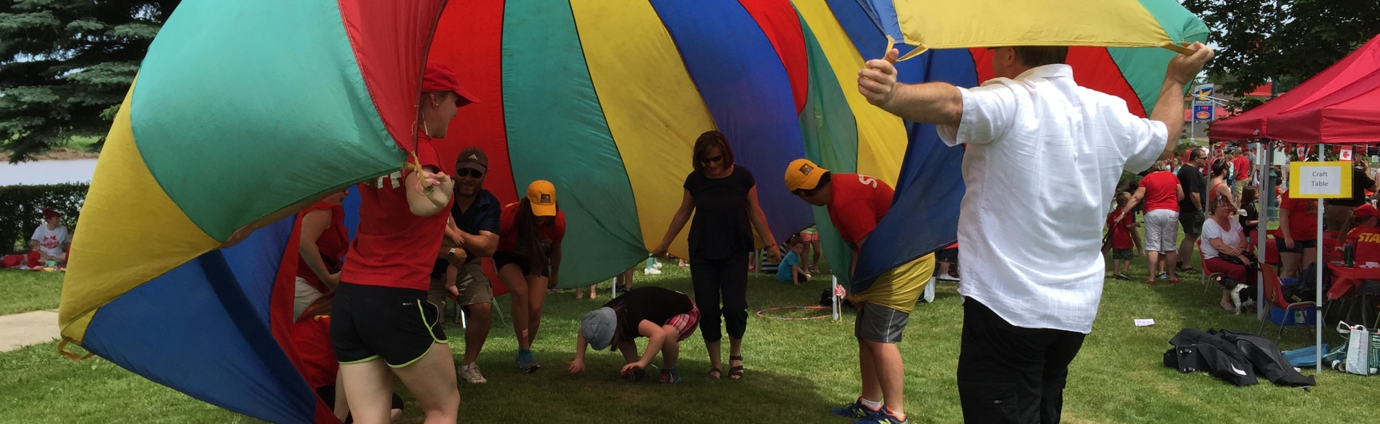 Youth playing under a parachute in the sun
