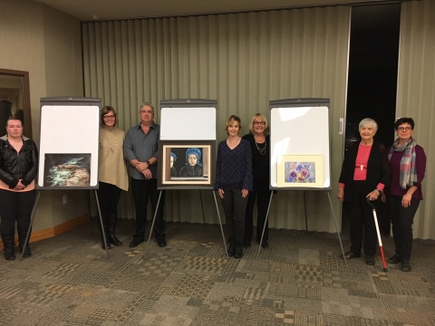Artists next to their paintings in Council Chambers