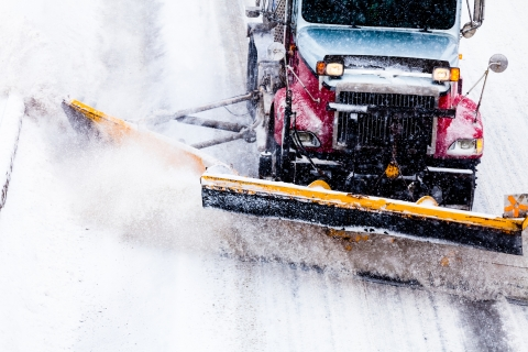 A snow plow clears snow from a road.