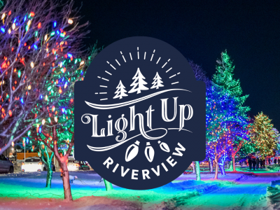 The Light Up Riverview logo appears over a photo of a snow-covered Riverfront Trail with trees lit an array of colours