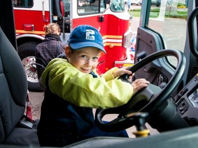Boy behind wheel of fire truck