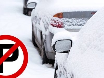 Vehicles parked on snowy road. A No Parking symbol is placed over the photo.